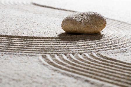 inner peace: zen sand still-life -single stone on sinuous waves for concept of beauty spa or spirituality with inner peace
