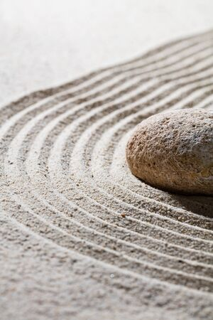 suppleness: zen sand still-life - textured stone on sinuous waves for concept of relaxation or meditation in beauty or spirituality, closeup Stock Photo