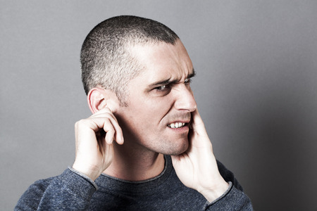 deafening: noise and hearing concept - thinking young man suffering from earache or toothache, touching his face for pain, contrast effects