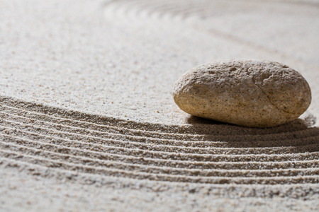 waves  pebble: zen sand still-life - textured pebble on sinuous waves for concept of wellbeing or beauty spa with inner peace, closeup