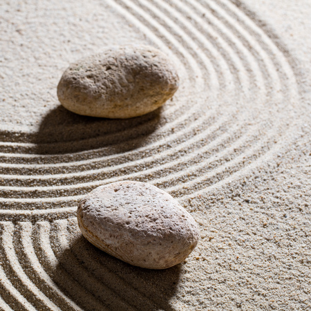 inner peace: zen sand still-life - textured stones set across sinuous waves for concept of different directions or change with inner peace, closeup