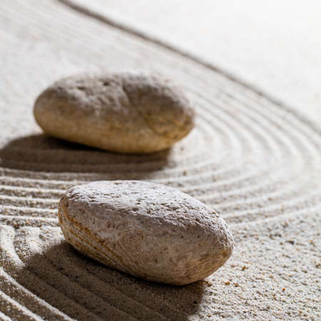 inner peace: zen sand still-life - stones set on sinuous lines for concept of progression or change with inner peace, closeup Stock Photo