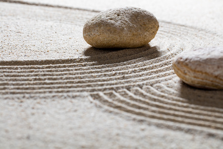 zen sand still-life - textured pebbles set across sinuous waves for concept of spirituality or beauty with inner peace