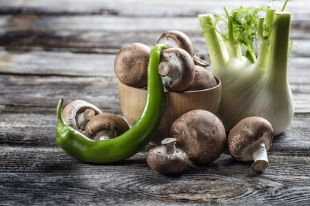 green pepper: vegetable still life - fresh Paris mushrooms, fennel and green pepper set on genuine wood background, studio shot