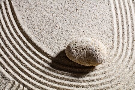 suppleness: zen sand still-life - one stone designing waves or a curve for concept of change or suppleness, top view Stock Photo