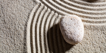 serenity: zen sand still-life - one stone at the intersection of different roads for concept of change or flexibility with serenity, top view Stock Photo