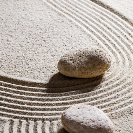 suppleness: zen sand still-life - two stones showing the direction for concept of evolution with care and peace, closeup
