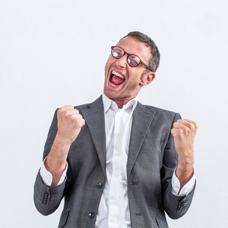 ecstatic: conviction concept - ecstatic middle aged businessman with dynamic body language screaming his victory, white background