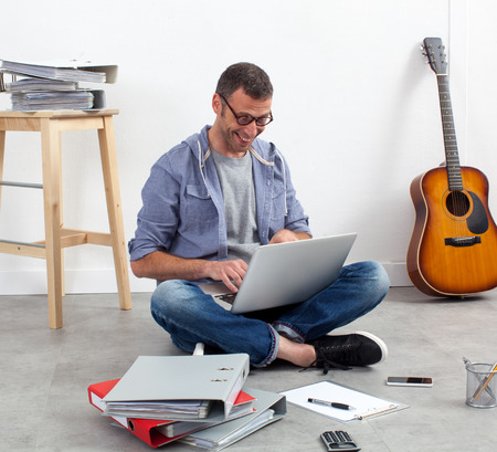 selfemployed: self-employment concept - happy self-employed man working his budget on computer with paperwork around the floor relaxing from home Stock Photo