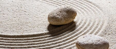 inner peace: zen sand still-life - textured stones set on sinuous waves for concept of steadiness or suppleness with inner peace