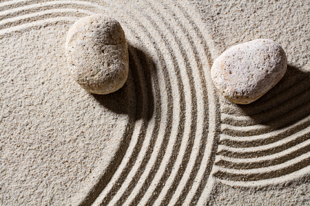 inner peace: zen sand still-life - two stones across lines to give different directions for concept of change or flexibility with peace, top view Stock Photo