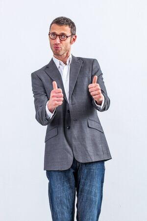 conviction: conviction concept - reserved middle aged businessman with eyeglasses and thumbs up standing for good management, white background Stock Photo