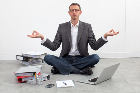 zen business concept - peaceful entrepreneur practicing yoga at the office, sitting crossed legs, seeking for inspiration in working on his budget