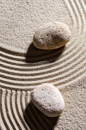 suppleness: zen sand still-life - two stones set across sand lines for concept of spirituality or serenity, top view