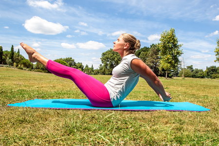 keep fit: fitness and slimming outside - sporty young blond woman working out to keep fit, lifting her legs and toning her abs on an exercise mat over summer blue sky Stock Photo