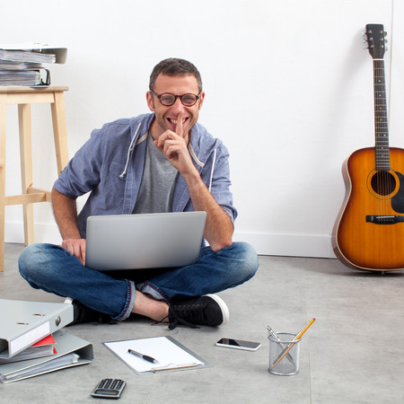 homeoffice: self-employment concept - smiling start-up businessman working his budget and music business sitting on the floor of his home-office