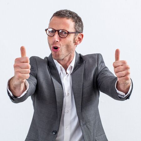 conviction concept - happy middle aged businessman with eyeglasses and thumbs up standing for satisfaction, white background Фото со стока