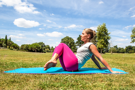 keep fit: fitness and slimming outside - active young blond woman working out to keep fit, toning her legs and waist on an exercise mat over sunny blue sky
