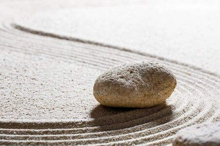 progression: zen sand still-life - single stone set on sinuous lines for concept of harmony or progression with care, closeup