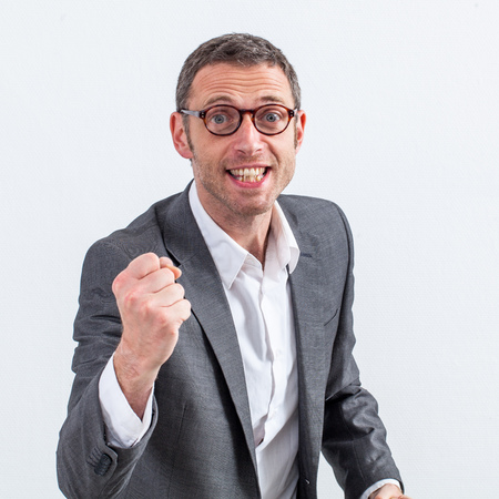 conviction: conviction concept - excited middle aged businessman with eyeglasses and fist in the foreground fighting for success, white background Stock Photo