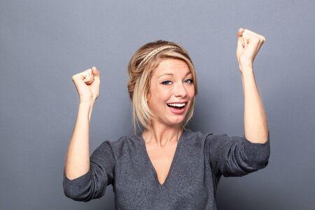 lenguaje corporal: el concepto de éxito - feliz mujer joven rubia de ganar una competición con el lenguaje corporal de la diversión y las manos arriba, estudio de fondo gris