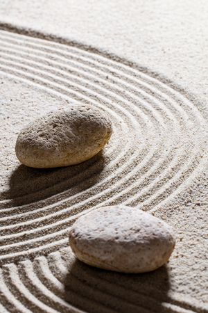 sinuous: zen sand still-life - textured stones set on sinuous waves for concept of change or suppleness with inner peace, closeup