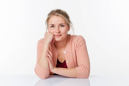 sparse: serene smile - peaceful young blond woman sitting in a sparse office expressing her wellbeing at work, white background studio
