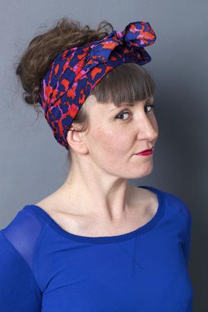 arrogancia: retrato femenino - retrato de una mujer joven que parece fresca con el peinado cincuenta disfrutando sonriente para la diversión, fondo gris Foto de archivo