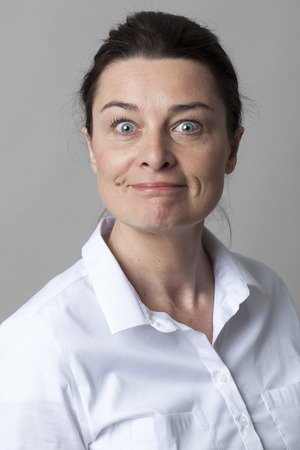 eyes wide open: female portrait - joyous smart mature woman smiling with elegance, looking with eyes wide open for surprise and joy, grey background