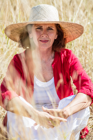 quietness: outdoors relaxation - thinking beautiful lady sitting in high dry summer field to enjoy quietness and sun protection,summer daylight Stock Photo