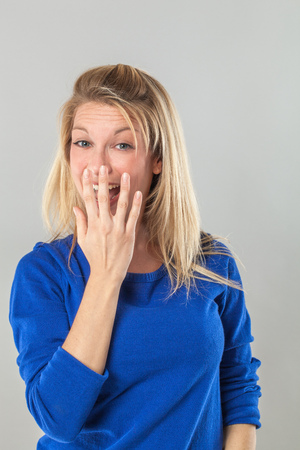 hidden success: successful smile - adorable young blond woman laughing with hand hiding her mouth for fun and joy, grey background studio