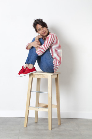 legs crossed: student vacation smile - playful young ethnic girl sitting on a stool with legs crossed frowning acting vexed, white background studio