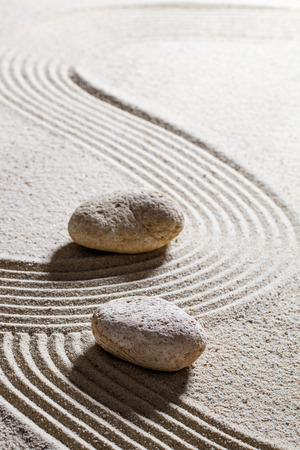 inner peace: zen sand still-life - two stones showing different directions for concept of evolution or progression with inner peace Stock Photo