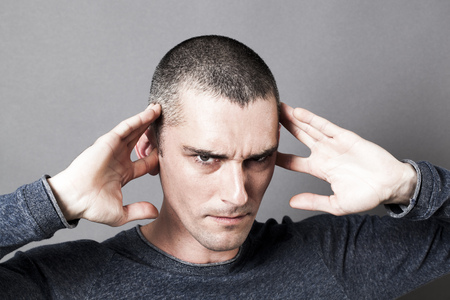 evil: noise and hearing concept - evil-looking young man plugging his ears to avoid listening to problems, contrast effects Stock Photo