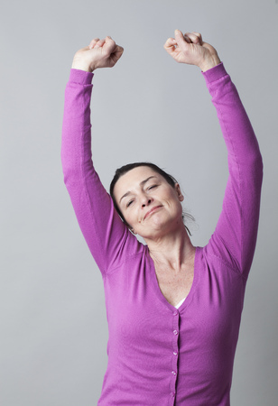 sleepiness: morning concept - happy mature woman stretching out, raising her arms up to wake up or relax, grey background studio