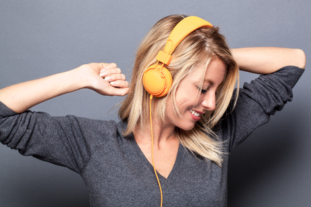 sexy headphones: sexy young blond woman listening to music on headphones, dancing with arms raised for energy, grey background studio