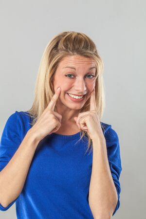 fake smile: cheeky young blond woman with a fake smile expressing her convictions and optimism or her white teeth for dental whitening experience Stock Photo