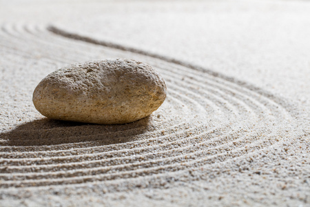 inner peace: zen sand still-life - textured stone on sinuous waves for concept of beauty spa or wellness with inner peace, closeup