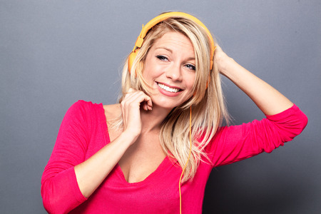 flashy: joyous young blond woman with flashy pink sweater listening to music on headphones, grey background studio