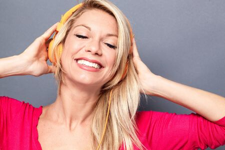 flashy: relaxed young blond woman with flashy pink sweater listening to music on headphones, grey background studio Stock Photo