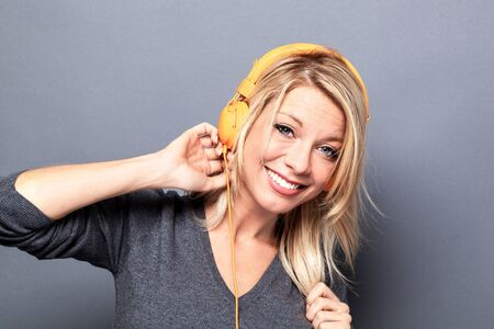 beat women: thrilled young blond woman listening to music on headphones, dancing for fun, grey background studio