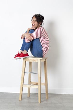 legs crossed: student vacation smile - cheeky young ethnic girl sitting on a stool with legs crossed acting surprised, white background studio