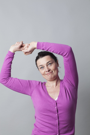 wellness sleepy: morning concept - successful mature woman stretching out, raising her arms up to wake up or to relax, grey background studio