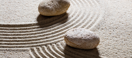 inner peace: zen sand still-life - stones set across sinuous waves for concept of different directions or change with inner peace Stock Photo