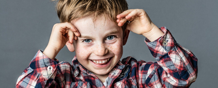 cheeky: portrait of a cheeky young male preschooler with freckles and blue eyes playing with his hands for fun childhood, textured effects on grey background studio Stock Photo