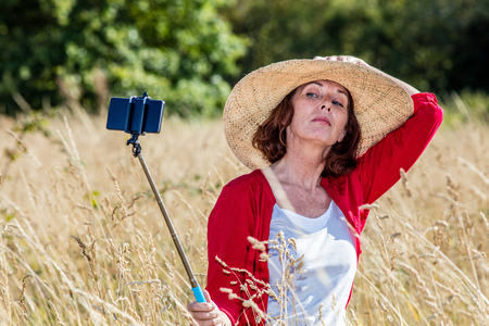 50s: outdoors selfie - arrogant 50s woman with big summer hat making a self-portrait on mobile phone on stick in the middle of summer high grass Stock Photo