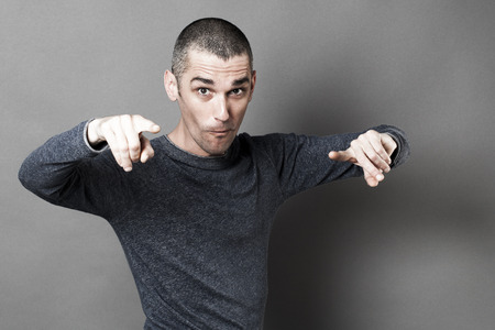 reproach: blaming concept - fun young man with short hair accusing or showing someone responsible with his fingers, grey background