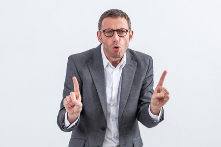 indexes: blaming concept - unhappy middle aged entrepreneur with eyeglasses warning or threatening someone with his indexes raised, white background