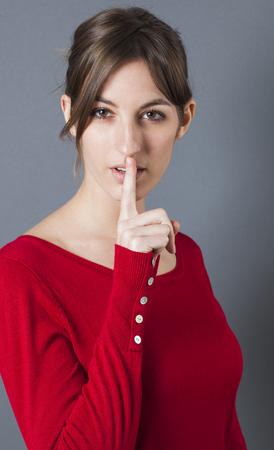 segreto di bellezza concetto - giovane e bella bruna tenendo le labbra strette per discrezione femminile o mistero sexy, sfondo grigio