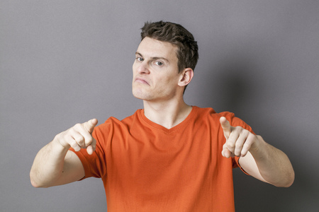 reproach: guilt concept - bossy young sporty man accusing or threatening someone with his hands for blame, grey background Stock Photo